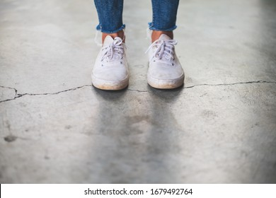 Closeup image of a woman wearing jean and white sneakers standing on concrete floor