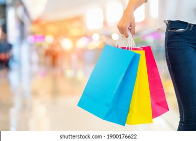 Closeup image of a woman's arm holding shopping bags in the mall