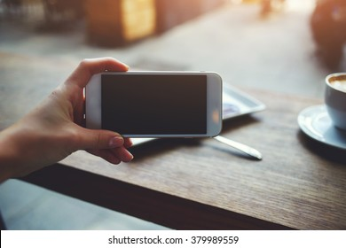 Closeup image of woman's hand holding mobile phone with blank copy space screen for your text message or promotional content, young female watching video via cell telephone while sitting in cozy cafe