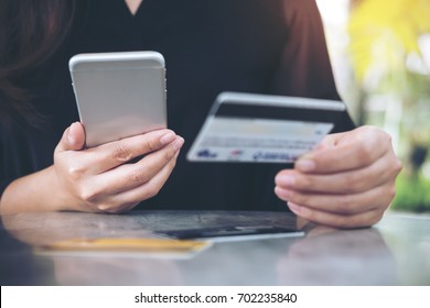 Closeup image of a woman's hand holding credit card and using mobile phone on the table in office