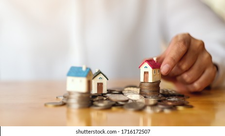 Closeup image of a woman's hand putting house model on pile of coins for saving money concept