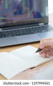 Closeup image of woman's hand writing on a blank notebook with laptop