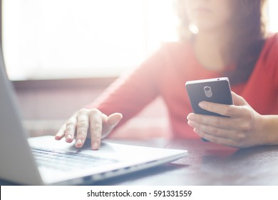 Closeup image of woman`s hands holding smart-phone and typing something at keyboard of laptop. Young female searching information in network on mobile phone and laptop during free time.