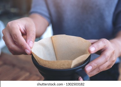 Closeup image of a woman's hands setting a filter to make a drip coffee on vintage wooden table