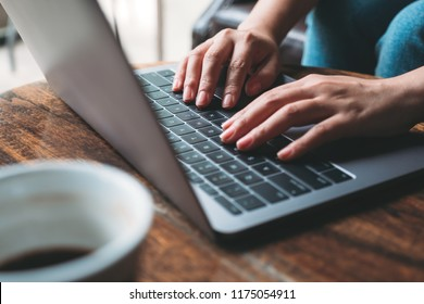 Closeup image of a woman's hands working and typing on laptop keyboard with coffee cup on wooden table