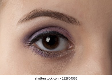 Close-up image of a woman's right eye with eye shadow