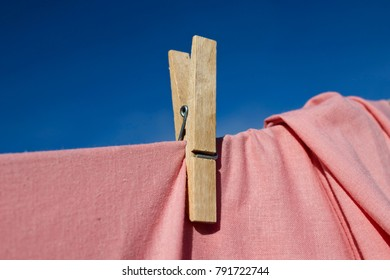 Closeup image of a wooden clothespin with a rose bed sheet.