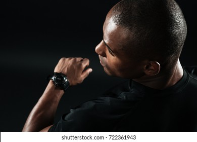 Close-up image of young afro american man dressed in black t-shirt standing over black background l