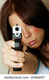 Close-up image of young attractive female pointing gun.  Focus is on barrel of gun.