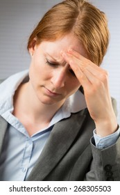 Closeup image of a young businesswoman with a headache or migraine.
