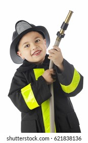 """Close-up image of a young elementary """"fireman""""  looking at the viewer while holding a hose, pointed and ready for the spray.  On a white background."""