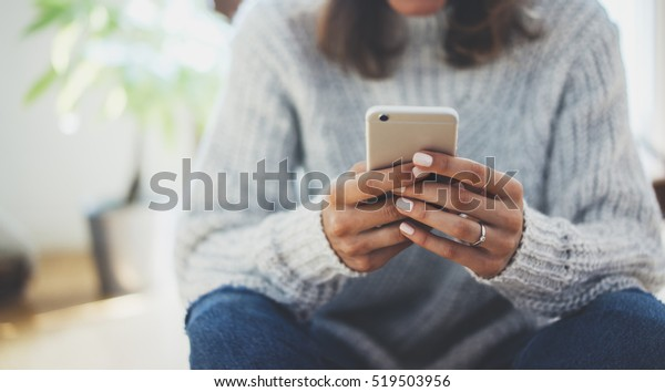 Close-up image of young hipster girl sitting at cozy home interior and using modern smartphone device, female hands typing text message via cellphone, social networking concept