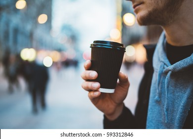 Close-up image of young hipster man walking at night city streets and drinking coffee to go outside, man wearing casual hoodie and enjoying his cappuccino
