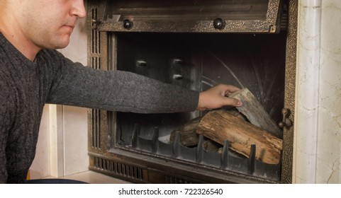 Closeup image of young man throwing wood in fireplace