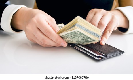 Closeup image of young rich woman trying to put big stack of money in tight wallet