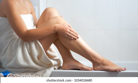 Closeup image of young woman covered in towel massaging legs in bathroom