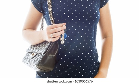 Closeup image of young woman with handbag holding keys from house