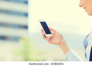 Closeup image young woman holding using smart mobile phone isolated outside corporate building background. People new generation technology addiction concept. Customer service provider relationship