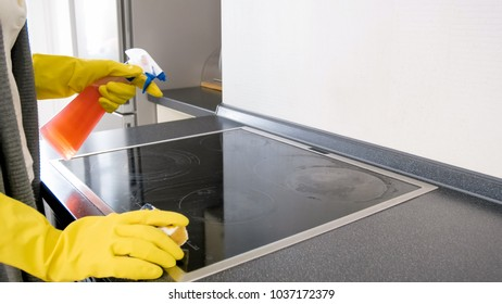 Closeup image of young woman in rubber gloves cleaning electric hob