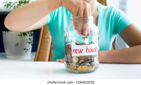 Closeup image of young woman throwing money in glass jar with savings for buying new house