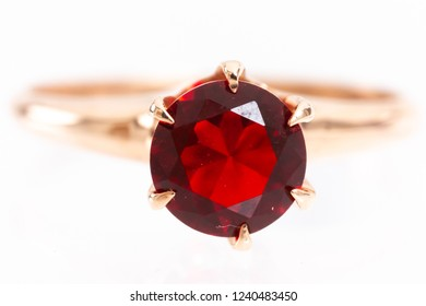 Closeup of imperfect ruby gemstone set in gold ring showing scratches