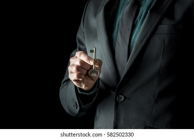 Close-up of incognito man in black suite, holding vintage key with two fingers, standing isolated on black background.