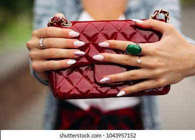 Close-up of incognito woman with elegant manicure wearing jewelry holding pretty small red bag.