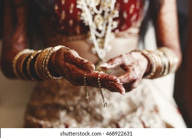 Closeup of Indian bride's hands covered with mehndi and holding a golden necklace