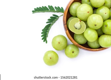 Closeup Indian gooseberry fruits ( phyllanthus emblica, amla ) in wooden bowl with green leaf and sliced isolated on white background. Top view. Flat lay.