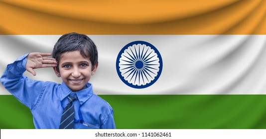 Close-up of a Indian kid saluting in front of the Indian flag