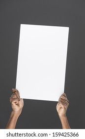 Closeup of an Indian man holding up a banner against a grey background. Cardboard placard is blank ready for your message.