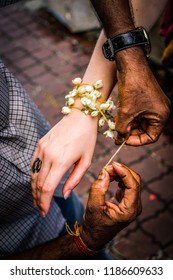 Close-up of an Indian man tying a Gajra bracelet of jasmine flowers around the wrist of a white woman, a symbol of love and romance in the Indian and Hindu cultures in Kuala Lumpur, Malaysia