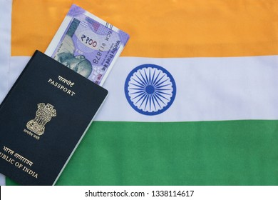 Closeup of Indian passport with Indian currency on Indian flag as a background