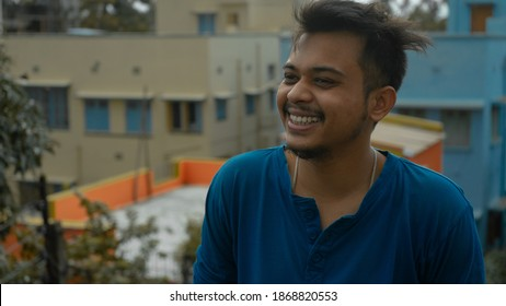 Closeup of an Indian young man posing laughing out loud. Relax profile picture with a confident smile on the face. Candid of an Indian boy laughing