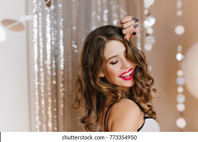 Close-up indoor photo of refined european woman with stylish makeup relaxing at birthday party. Portrait of chilling curly girl with dark hair posing near sparkle decoration.