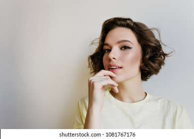 Close-up indoor portrait of lovely girl with dark hair. Studio shot of graceful pale young woman with short haircut isolated on white background.