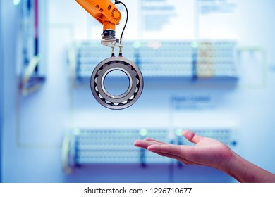 Close-up Industrial robotic gripping a workpiece for send to human hand on smart factory blue tone color blurred background and copy space, industry 4.0 and smart AI technology concept
