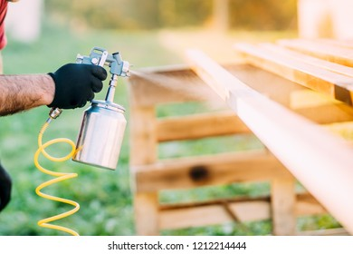 close-up of industrial worker hand using paint gun or spray gun for applying paint on brown timber wood