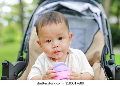 Close-up infant baby boy sitting on stroller and drinking water from Baby sippy cup with straw.