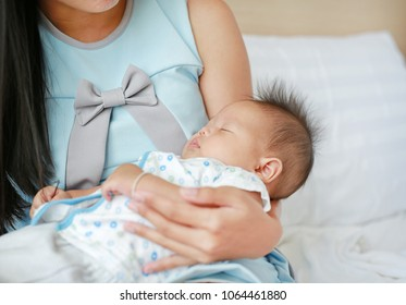 Closeup infant baby sleeping in mother arms.