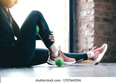 Close-up inflated legs in leggings. The girl leans a hip on the green Ball Myofascial. Massage of the thighs