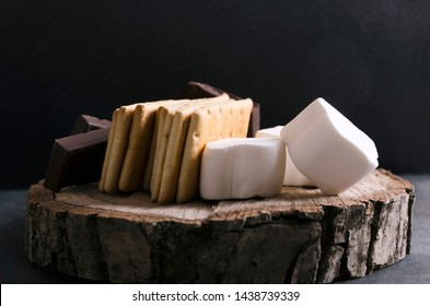 Closeup of ingredients for tasty s`mores with chocolate nad marshmallows on the wooden tray, rustic mood