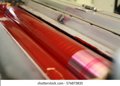 Closeup of the ink rollers magenta of a printing press offset machine