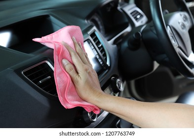 Closeup of inner side car cleaning  with pink  microfiber cloth by woman owner's hand in sunny day. The lovely simply family activity.