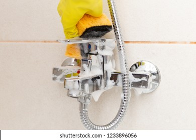 Close-up inox shower water tap being cleaned with orange sponge by person wearing gloves