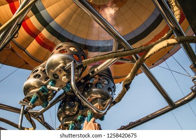 Closeup of the inside of a hot air balloon and a hand operating the flamethrower with flames. Travel, air, transport, aviation, trip, adventure, summer concept.
