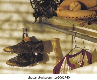 Closeup of the inside of an old timers baseball locker, with warm side light. Focus is on the scuffed and worn spikes hanging from a nail in the wall.  Items include, mitt, bat, catchers mask, jersey