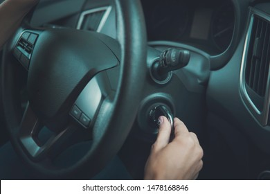 Closeup inside vehicle of female hand holding key in ignition. Woman starting engine of car turning key. Steering wheel and female starting automobile. Girl has come to destination and stops car.