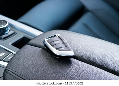 Closeup inside vehicle of wireless key ignition. Start engine key. Car key remote in black perforated leather interior. Modern car background. Modern car Interior details. Car detailing. Keys close up