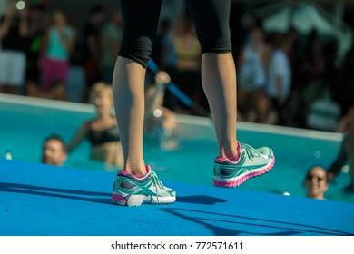 Close-up of Instructor Legs at Swimming Pool Edge: Aqua Aerobics Workout.